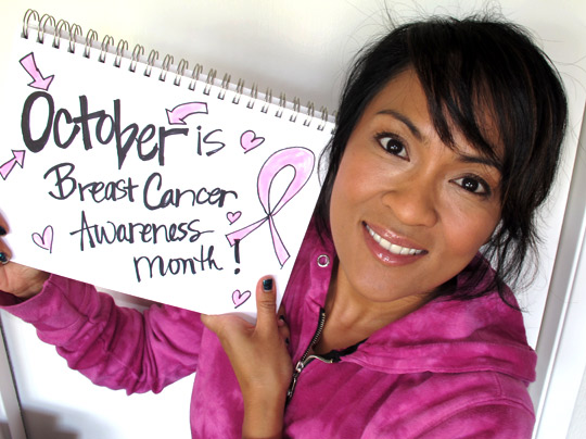 karen from makeup and beauty blog holding her october is breast cancer awareness sign