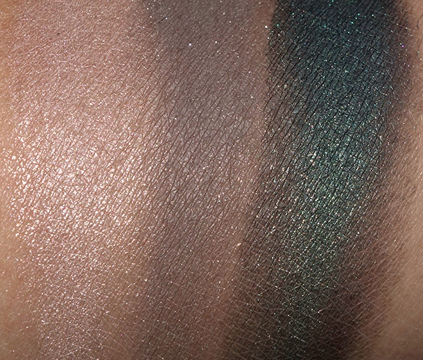 Too Faced Rock N Roll Palette Swatches from the left: New Romantic (a shimmery golden peachy taupe), Glam Rock (a satiny medium gray with silver glitter) and Punk (a shimmery blackened forest green)