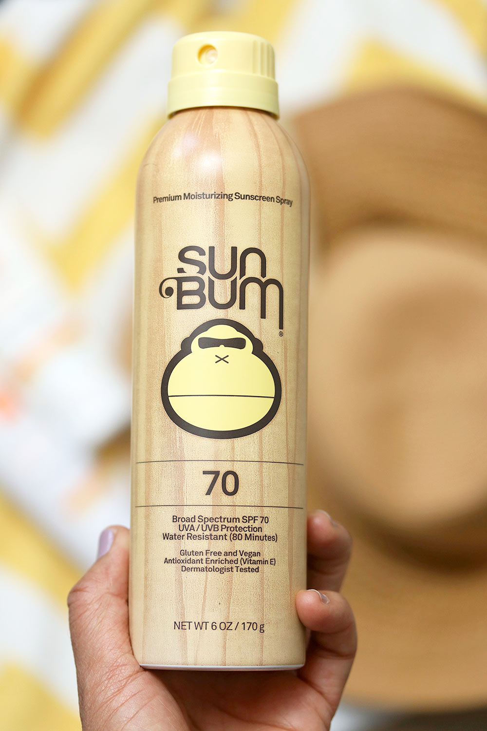 sun bum spray in hand